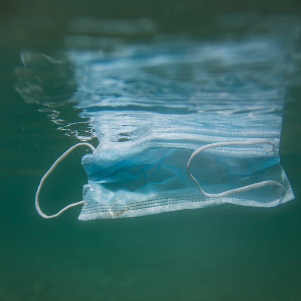 PPE mask floating in water